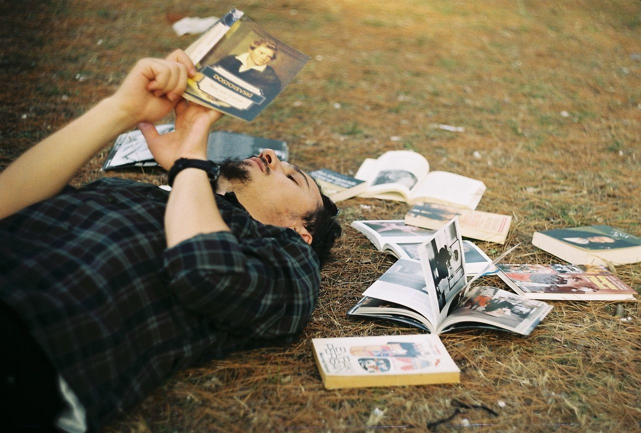 High angle view of man reading book while relaxing on field