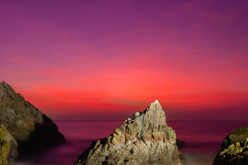 waves hit the big cone shape rock in the middle of stone cape during sunset at banana beach Phuket Cone Cone Shaped Stone, Rocky Mountains Stone Cape, Dracula, Venice Red,sky, Island, Wave, Sea, Edit, Travel, Sunset, Middlw, Banana Beach, Beauty In Nature Scenics - Nature Sky Tranquil Scene Rock Tranquility Nature Sunset No People Solid Sea Rock - Object Idyllic Water Non-urban Scene Outdoors Rock Formation Copy Space Land Purple