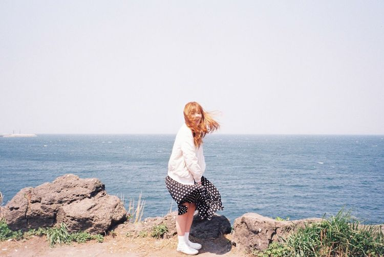 EyeEm Selects One Person Young Adult Long Hair Sea Rock - Object Young Women Horizon Over Water Happiness Beautiful Woman Looking At Camera Redhead Leisure Activity Casual Clothing Standing Smiling Outdoors Nature Real People Portrait Water JEJU ISLAND  Film Film Photography EyeEmNewHere