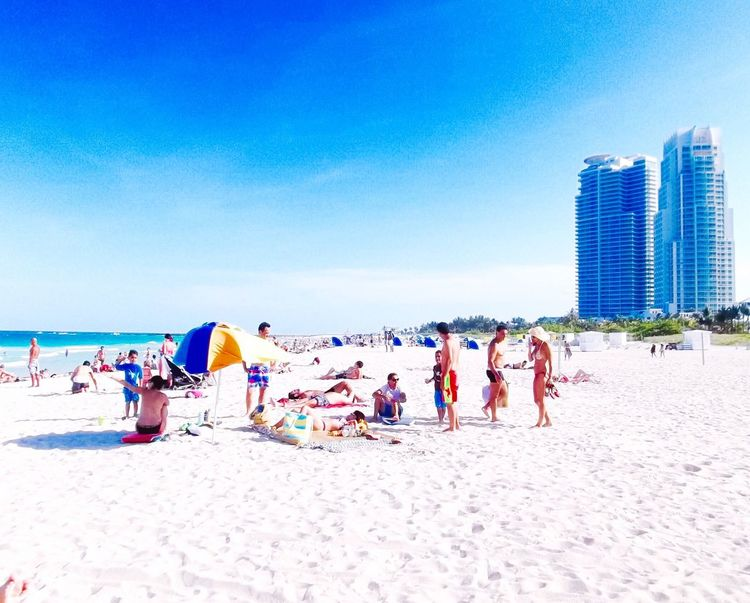 Relaxing on the pure white sandy beach White Sand Beach Blue Sky Ocean Water Buildings People Together Women Men Children Vacation Time Sunbathing Summer Beach Umbrella Family People Together By August 3 2016 Athleisure Colour Of Life Two Is Better Than One Two Tall Buildings Fatherhood Moments People And Places