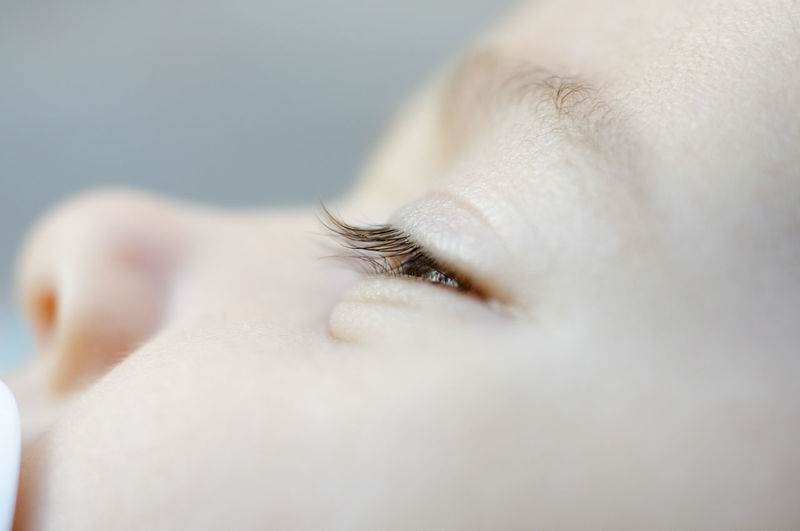 Close-up of cute baby girl with teardrop on face