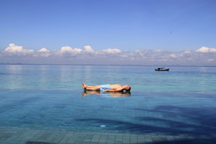 Full length of shirtless man resting on infinity pool by sea against sky