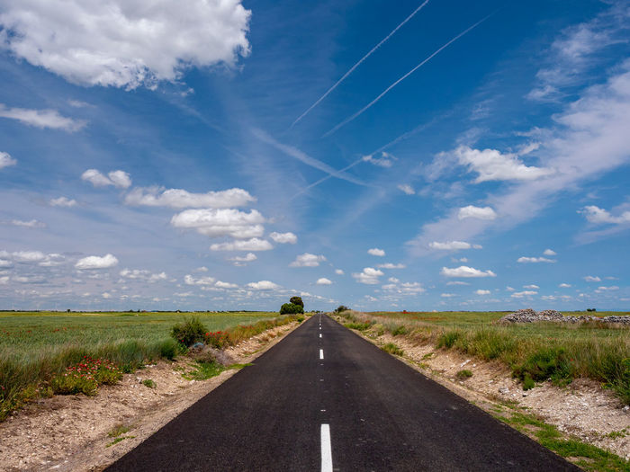 Road leading towards landscape against sky