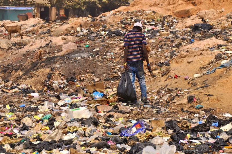 Rear view of man standing on garbage