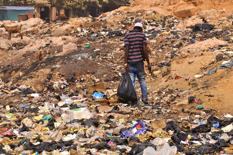 Rear view of man standing at garbage dump
