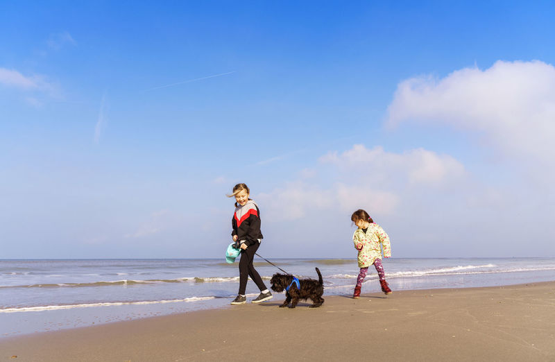 People with dog on beach against sky
