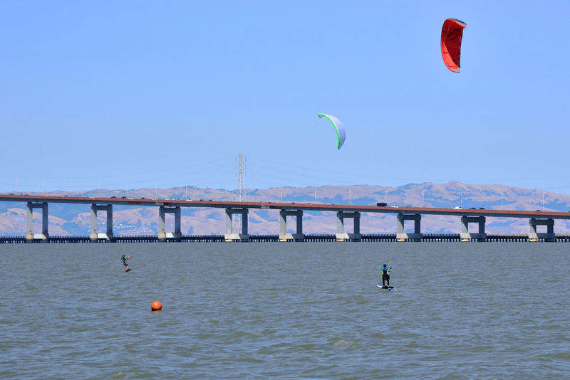 Kiteboarding In San Mateo 18 San Mateo, Ca. The Color Of Sport Kitesurfers Kiteboarding San Mateo Bridge Power Towers Power Lines Bridge Span Traffic On Bridge Colorful Sails Wind Power Watersports Aquactic Sports Sports Eastbay Hills San Francisco Bay Kitesurfing Clear Blue Sky Calm Waters Course Marker Leisure Activity Enjoying Life
