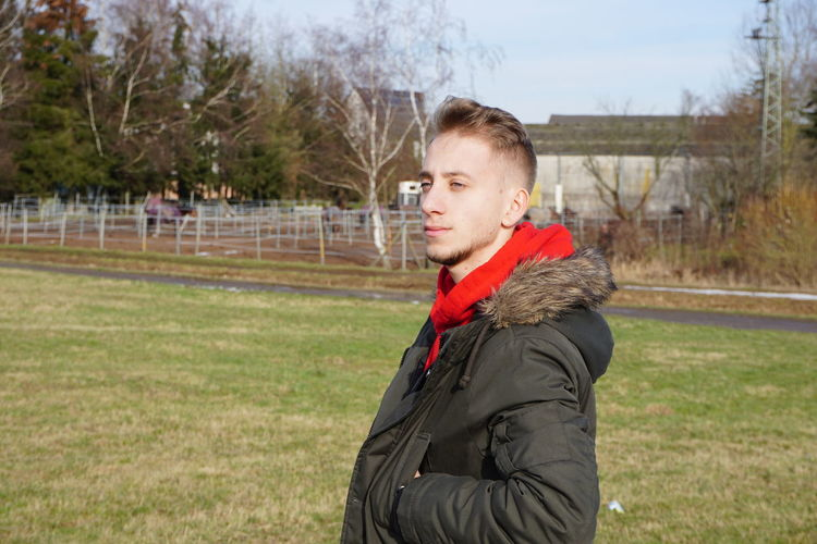 Young man looking away while standing in park