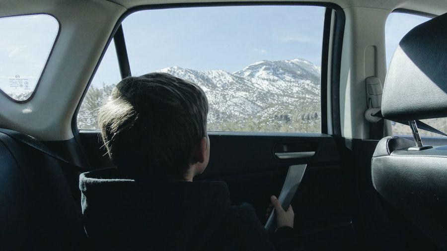 Side view of boy sitting in car