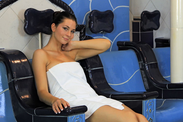 Portrait of young woman sitting on seat at spa
