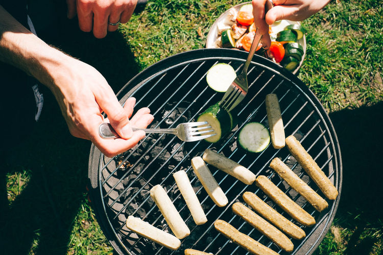 High angle view of people cooking food on barbecue grill