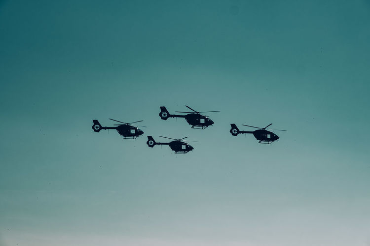 Silhouette of helicopters against clear sky