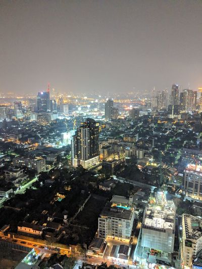 High angle view of illuminated city buildings against sky