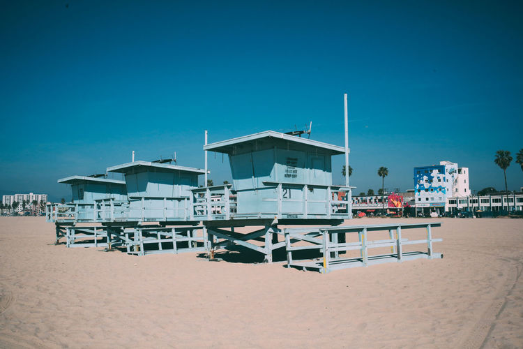 Lifeguard huts at beach against blue sky