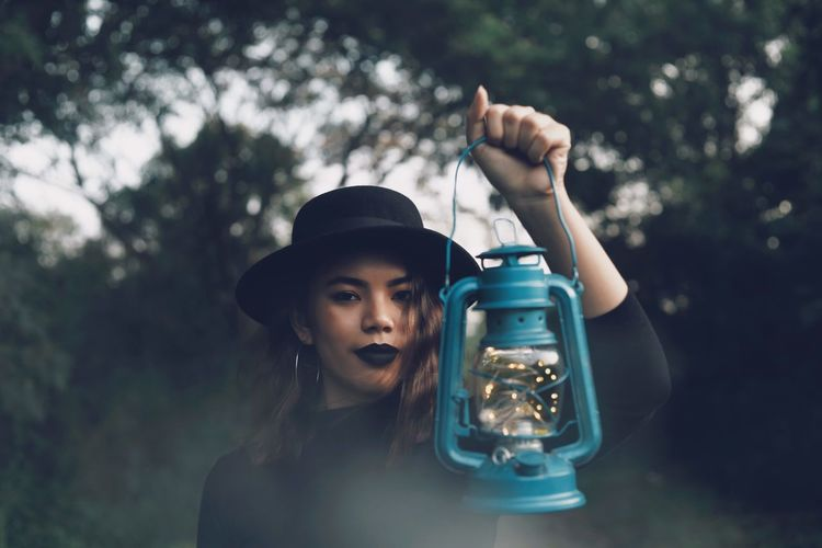 Portrait of woman holding old lantern against trees