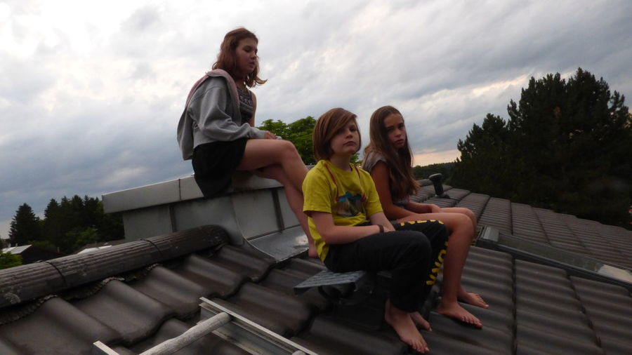 Siblings sitting on roof against cloudy sky during sunset