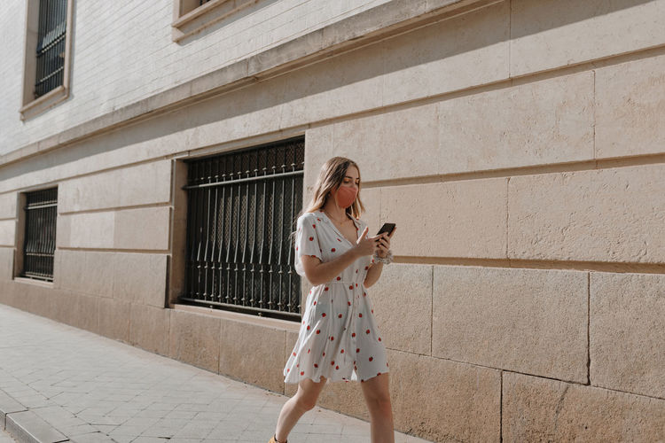 Full length of woman using mobile phone while standing against wall