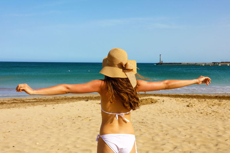 Rear view of woman wearing bikini while standing with arms outstretched at beach against sky