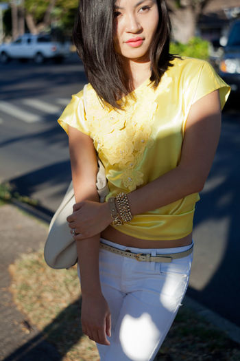 Close-up of smiling young woman holding yellow while standing outdoors