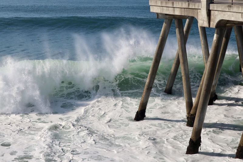 Waves crashing underneath a pier Water Sea Motion Wave Aquatic Sport Surfing Nature Sport Day Beauty In Nature Beach Land Outdoors Scenics - Nature Splashing Built Structure Power In Nature Architecture Flowing Water Breaking