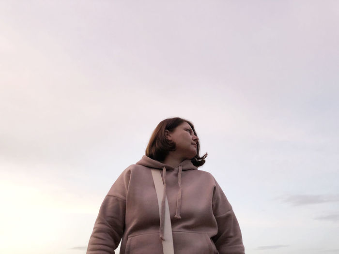Low angle view of young woman looking away against sky during sunset