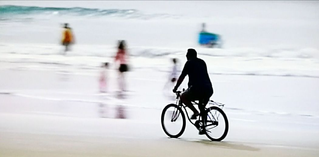 Man with bicycle on snow against sky