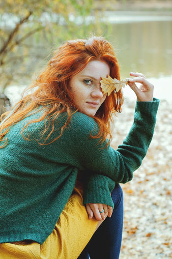 Portrait of redhead woman with freckles  holding leaf outdoors