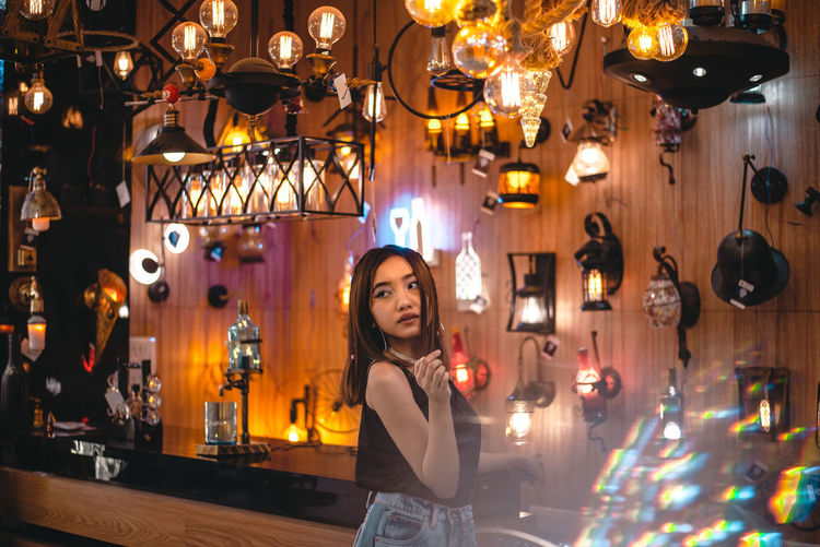 Portrait of young woman standing against illuminated lights