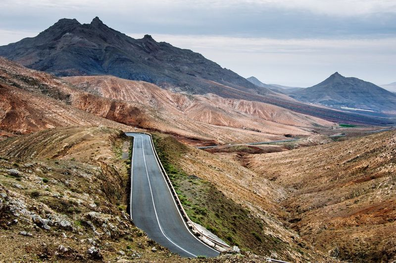 Scenic view of empty road through mountains against cloudy sky