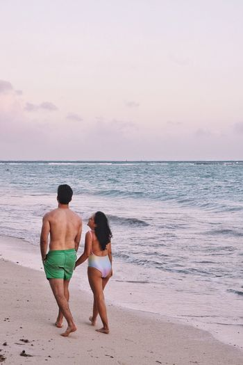 Man And Woman Walking On Shore Against Sea At Beach