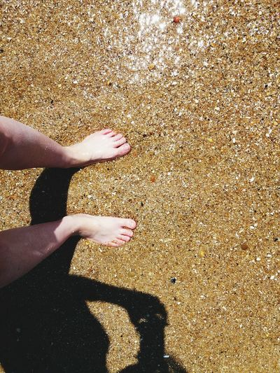 Low Section Of Person Standing On Sand At Beach During Summer