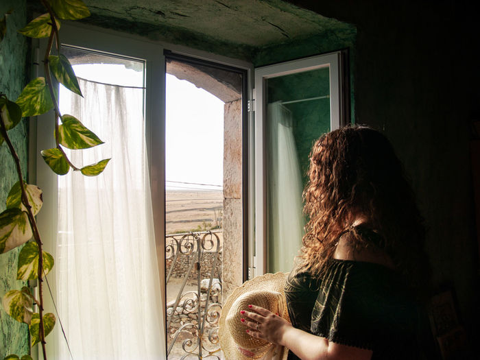 Side view of woman looking through window at home