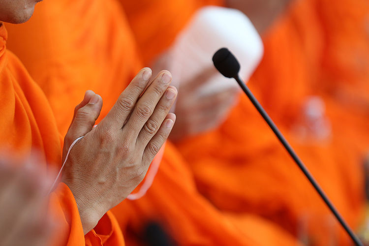 Cropped Image Of Monk With Hands Clasped By Microphone
