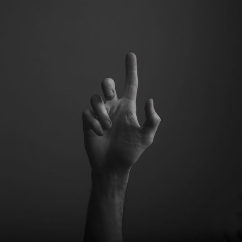 Close-up of human hand gesturing against black background