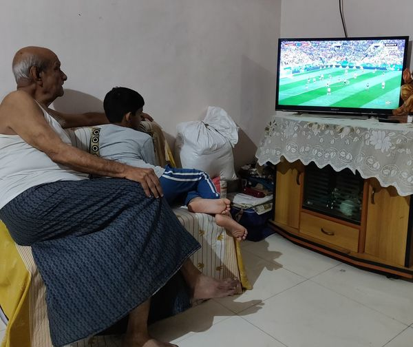 Grandfather And Grandson Watching Tv At Home