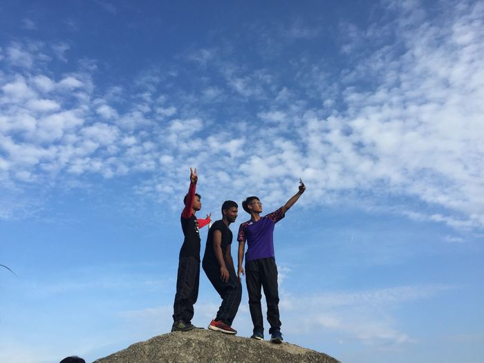 Low angle view of friends with peace sign taking selfie against sky