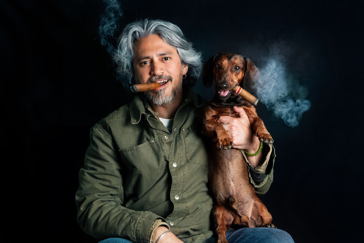 Portrait of man with dog smoking cigar over black background