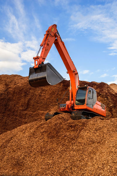A backhoe working on a pile of wood chips for industrial usage, paper production. Bulldozer Excavator Industrial Industry Machine Machinery Tractor Alternative Backhoe Biomass Crawler Digger Engineering Equipment Factory Lumber Material Paper Production Pieces Sawdust Scoop Timber Wood Chips Woodchip Woodchips