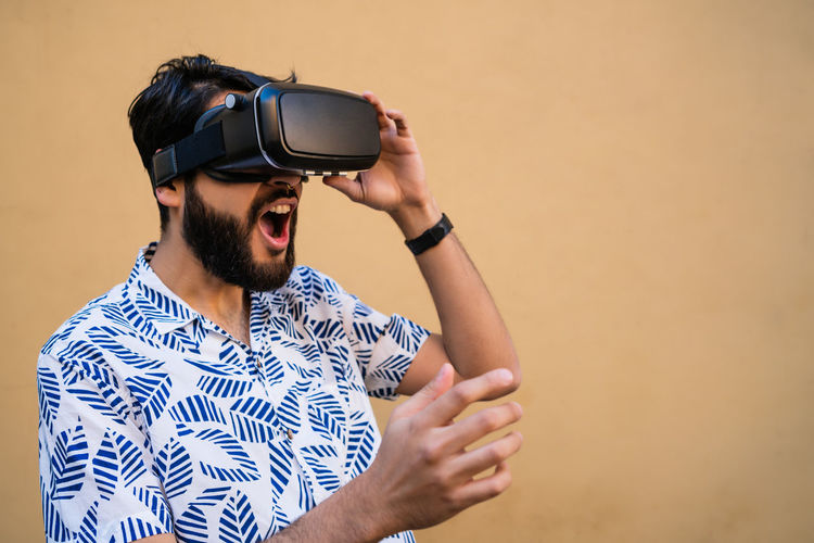 Young man using virtual reality simulator while standing by wall outdoors