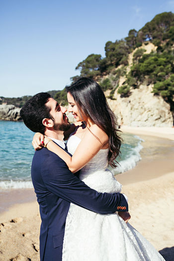 Happy Newlywed Couple Romancing At Beach Against Clear Sky