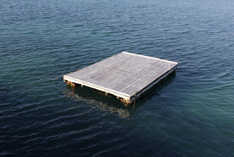 High angle view of wooden raft floating on water in sea