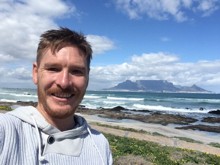 Portrait of smiling man standing at bloubergstrand against table mountain