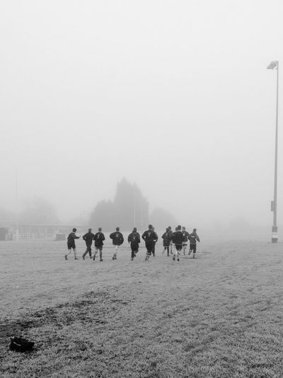 Rugby Players Warming Up Together Against Clear Sky During Foggy Weather