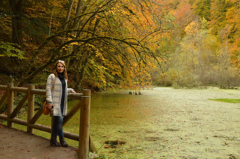 Woman standing by algae covered lake at yedigoller national park during autumn
