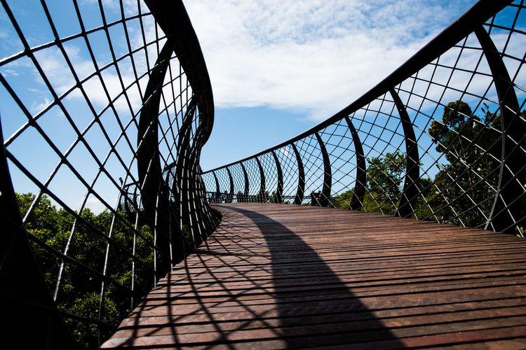 Low angle view of footbridge against sky