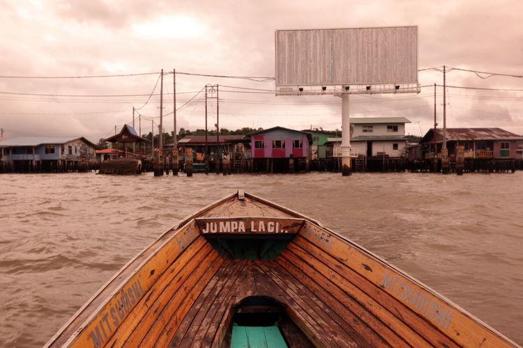 Cropped Image Of Boat On River Against Stilt Houses