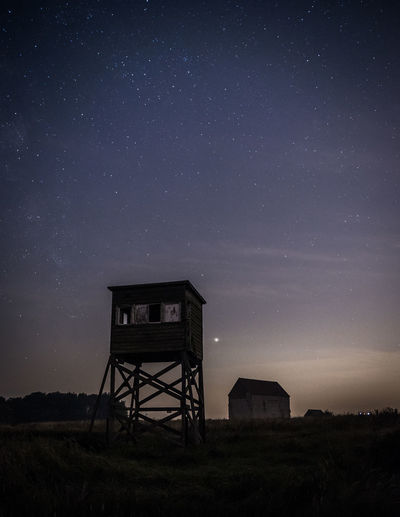 Tower on field against sky at night