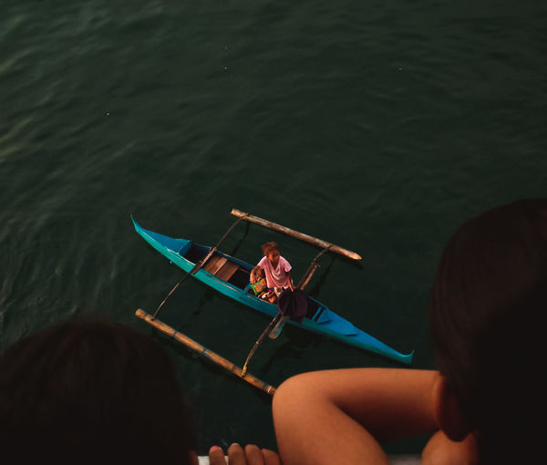 High angle view of people sitting on boat in sea