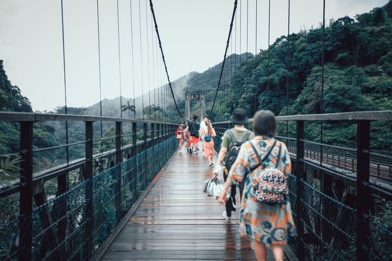 Rear view of people walking on footbridge
