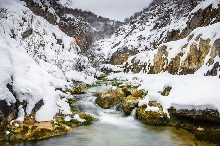 Scenic view of stream amidst snowcapped mountains during winter